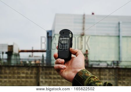 Dosimeter At Hand And Nuclear Power Plant On The Background