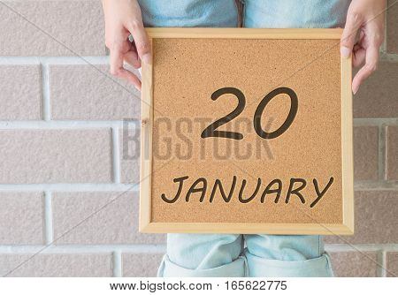 Closeup calendar at the cork board in hand of asian woman in front of her legs with 20 january word on brick wall textured background