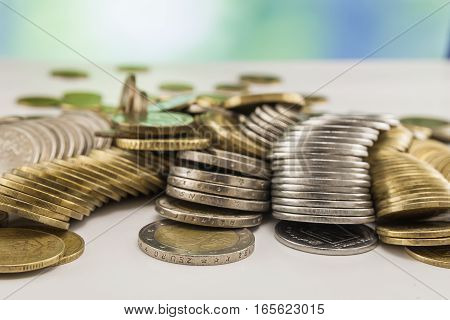 Growing coins stacks with green and blue sparkling bokeh background. Financial growth saving money business finance wealth and success concept.