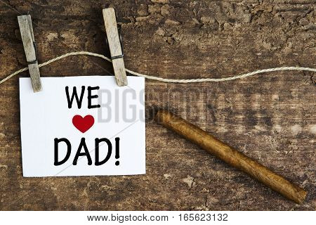 cigar on wooden plank and white sign with the words We Love Dad