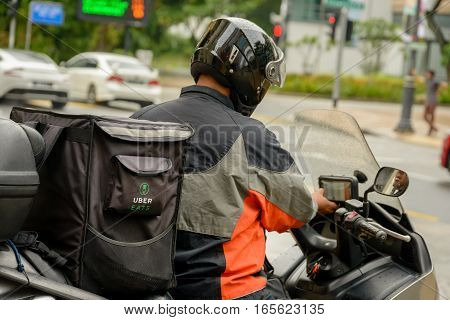 SINGAPORE - OCTOBER 07 2016: An Uber Eats motor scooter delivery rider prepares to set off to deliver a food order to a client.