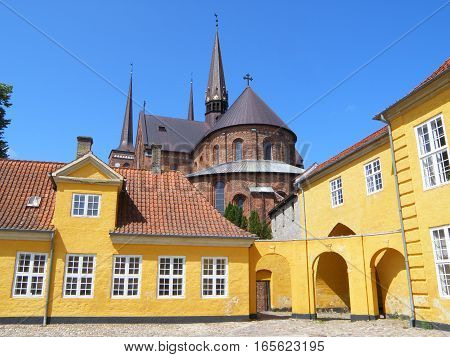 Yellow Palace and Cathedral of St. Luke (Roskilde Cathedral) under Vivid Blue Sky, Roskilde, Denmark