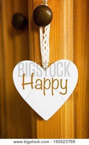 white wooden heart hanging from wooden door with the word Happy
