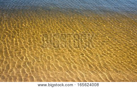 Clean, clear water in the river with a sandy bottom close up