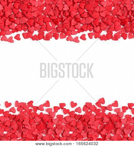Horizontal seamless background with copy space red hearts candy sprinkles isolated over white.