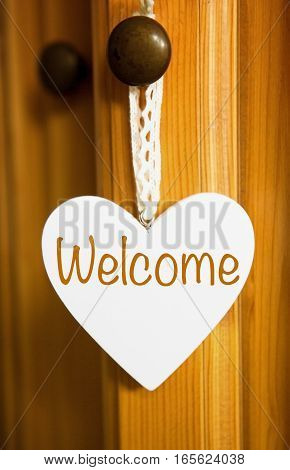 white wooden heart hanging on door knob with the word Welcome