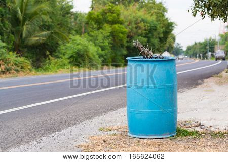 Blue dustbin or trashcan beside the road.beside the road or street.