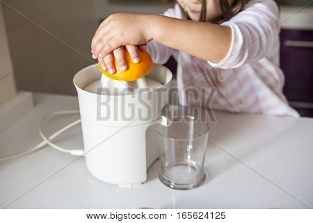 Little girl squeezing orange juice with a juicer in the kitchen