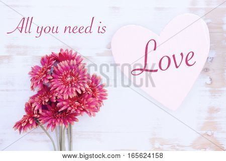 beautiful red flowers with wooden heart and the words All You Need Is Love