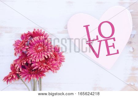 beautiful red flowers and wooden heart with the word Love
