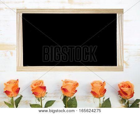 orange roses on white wooden background and black chalkboard