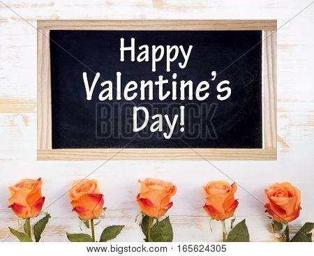 orange roses on white wooden table with chalkboard and the words Happy Valentines Day