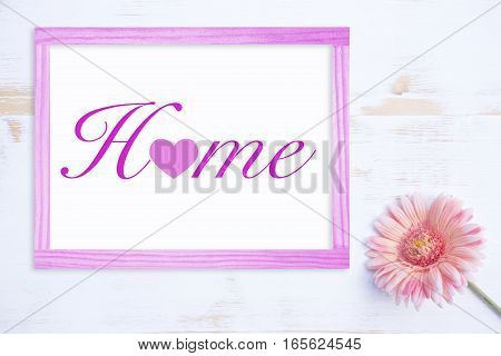pink flower on white wooden table and frame with the word Home