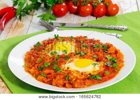 Shakshuka Eggs On White Plate With Knife And Fork