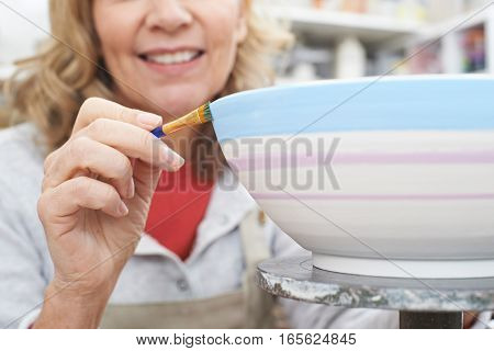 Mature Woman Decorating Bowl In Pottery Class