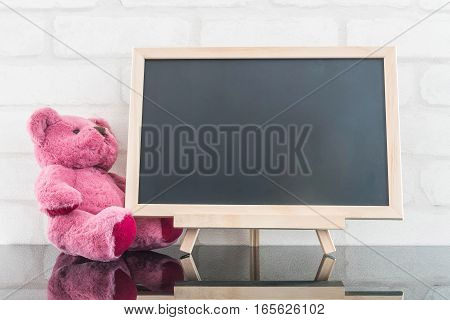 Closeup wood black board with pink bear doll on black glass table and white brick wall textured background