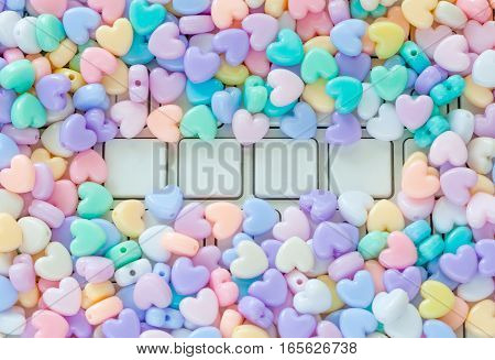 Valentines theme blank white keyboard buttons for (LOVE) text with small colorful pastel heart shaped plastic beads border use as background.