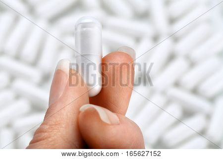 Hand with capsule on blurred background. Close up high resolution product. Health care concept.