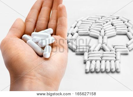Stop Drugs! Hand with white capsules next to the skull symbol of capsules. High resolution product. Drug abuse concept
