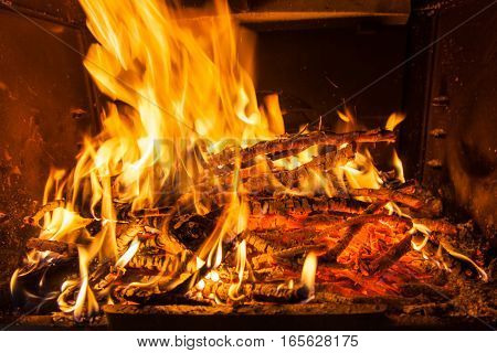 Burning firewood in the fireplace closeup texture of fire and flame