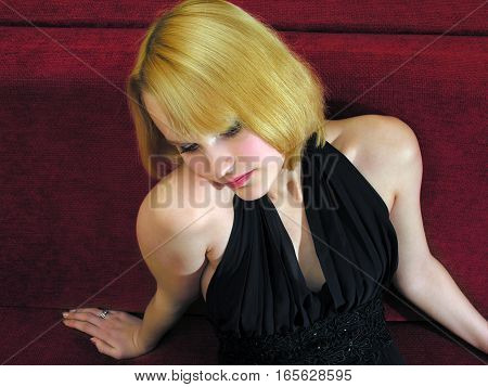 portrait of young attractive woman sitting on red sofa
