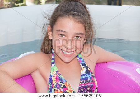 Teenage Girl Enjoys The Pool With A Buoy