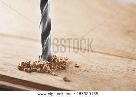 metal drill bit make holes in a wooden oaks plank
