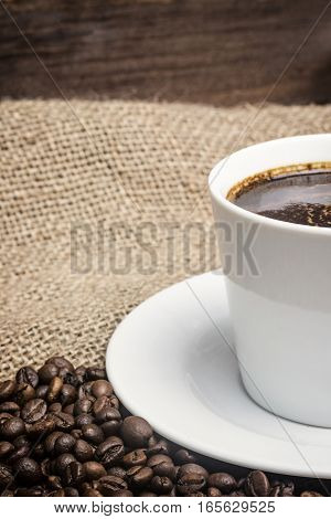 White cup of coffee standing on the sackcloth. Around it are scattered coffee beans and wooden desk is in the background. Vertically.
