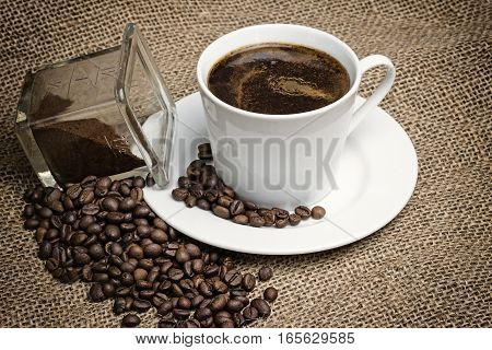 Higher angle view of the vintage photo of the white cup of coffee standing on the sackcloth. Around it are scattered coffee beans and ground coffee glass