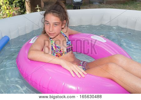 Girl Is In The Pool With Her Pink Buoy