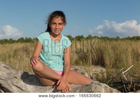 Girl Is Sitting On The Sand At The Top Of The Dune