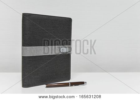 Black notebook and pen on the white table with copy space