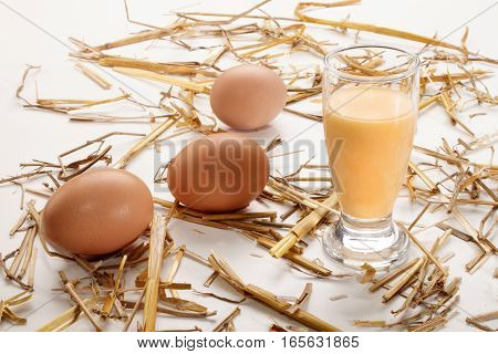 glass filled with egg liqueur and eggs and straw