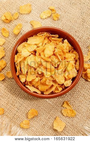 corn flakes in a brown bowl on jute