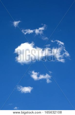 Beautiful white clouds in central part on clear blue sky. Vertical photo