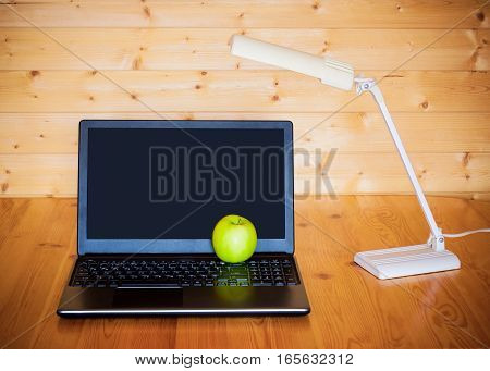 Place of work with laptop on table and lamp.