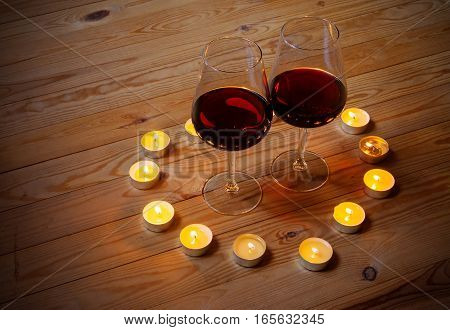 Red wine with candles on wooden background