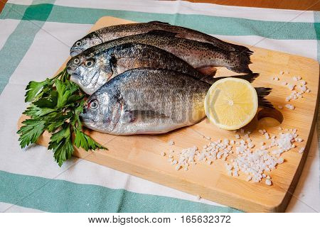 Fresh fish and lemon on wooden cutting board
