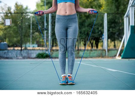 Woman in sportswear exercising with jump rope on the stadium