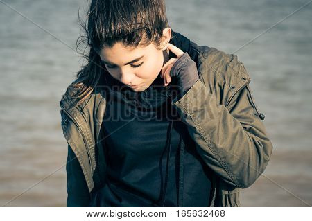 Outdoor portrait of a pretty teenage girl wearing khaki parka and walking on the beach