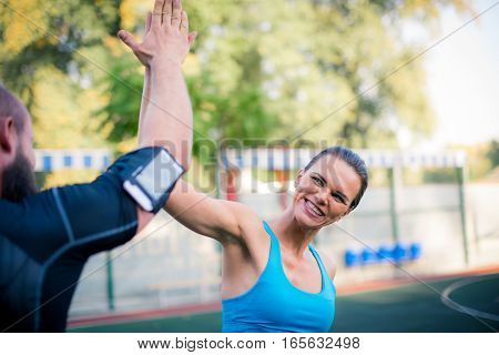 Happy couple workout together on the stadium and giving high five