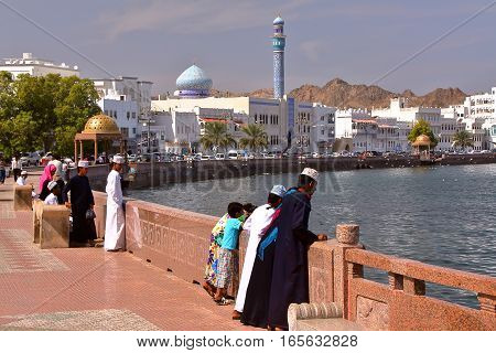 MUSCAT, OMAN - FEBRUARY 10, 2012: Muttrah corniche in Muscat with Omani young boys traditionally dressed