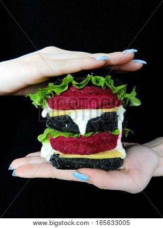 Vegetarian black burger with beetroot cutlet in the girl`s hands