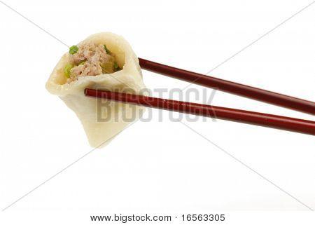 taking asian dumpling with chopsticks.