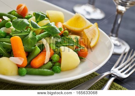 Salad with baby carrots peas onions and potatoes served on white plate on black wooden background