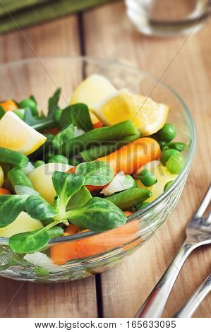 Salad with baby carrots peas onions and potatoes in glass bowl on wooden background