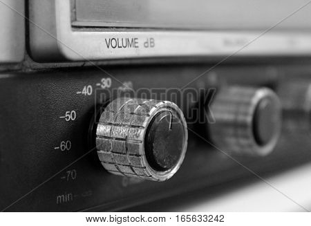 Close up of volume knob button on vintage stereo, black and white.