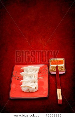 Asian Dumplings with dipping sauces on a vintage background