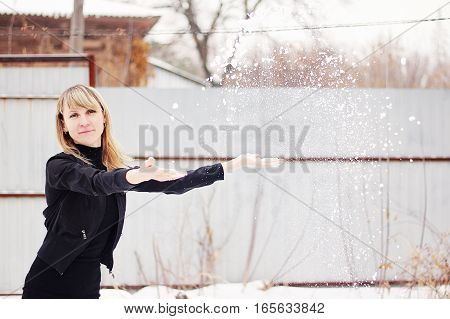 Beautiful woman throwing snow in the winter.