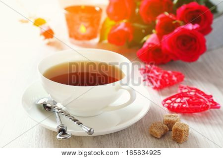 Valentine's Day: romantic morning tea drink with burning candle and bouquet of red roses. Toned image